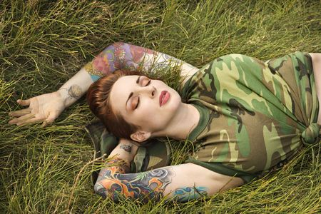 Attractive tattooed Caucasian woman in camouflage lying on grass in Maui, Hawaii, USA. photo