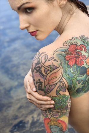 Back view of sexy  tattooed Caucasian woman by tidal pool in Maui, Hawaii, USA.