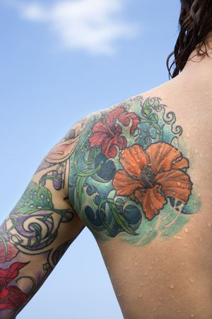 Close-up of Caucasian womans back and shoulder covered with floral tattoos. photo