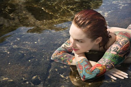 redhead: Sexy  tattooed Caucasian woman lying in tidal pool in Maui, Hawaii, USA. Stock Photo