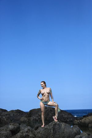 Sexy tattooed Caucasian woman standing on rocks in Maui, Hawaii, USA.