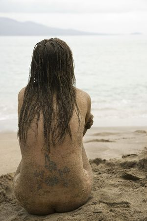 half nude: Rear view of Caucasian young adult nude woman sitting on beach. Stock Photo