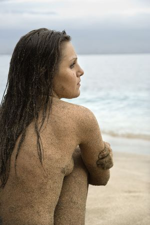 half nude: Side view of Caucasian young adult nude woman sitting on beach.