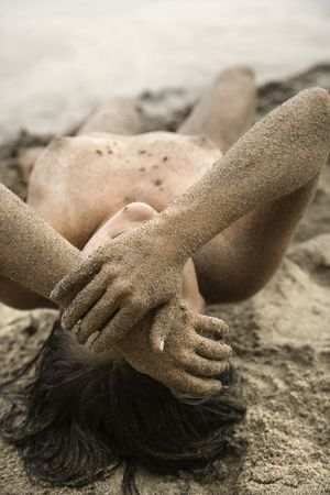half nude: Sexy Caucasian young adult nude woman lying on beach. Stock Photo