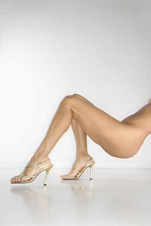 Lower half of  woman wearing high heel shoes against white background. photo
