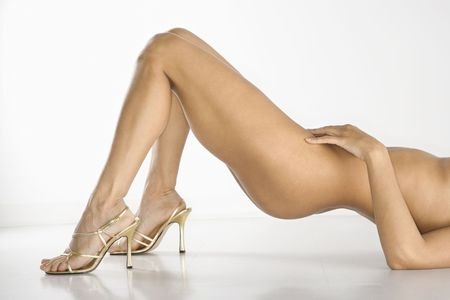 Lower half of nude woman wearing high heel shoes against white background. Stock Photo