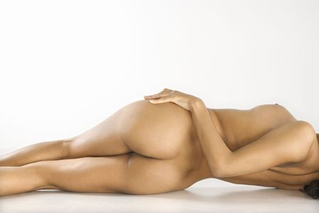 nude: Back view of attractive nude woman lying on floor against white background.