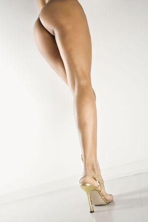 nalga: Opini�n trasera la mujer desnuda atractiva que est� parada en zapatos altos del tal�n.