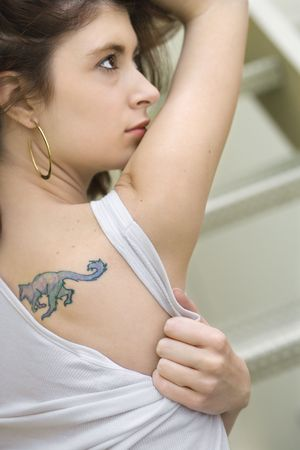 woman profile: Portrait of attractive young redhead Caucasian woman with tattoo on shoulder.