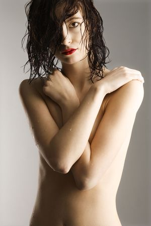 modesty: Portrait of bare attractive Caucasian redhead young woman with wet hair and skin. Stock Photo