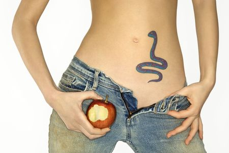 Portrait of attractive Caucasian young woman holding apple by snake tattoo on stomach. photo