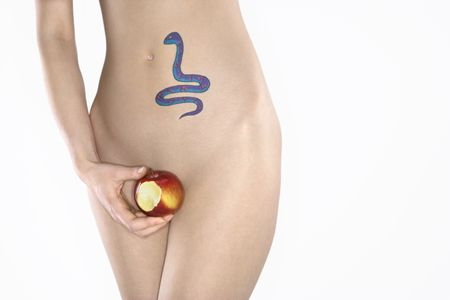 Portrait of nude attractive redhead Caucasian young woman with snake tattoo holding apple.