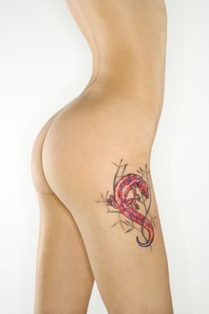 thighs: Portrait of nude attractive redhead Caucasian young woman with lizard tattoo.