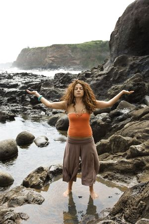 Young adult female standing on rocky shore with arms outstretched and eyes closed. photo