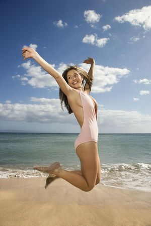 Pretty smiling young Caucasian woman in swimsuit jumping into air at beach in Maui Hawaii.
