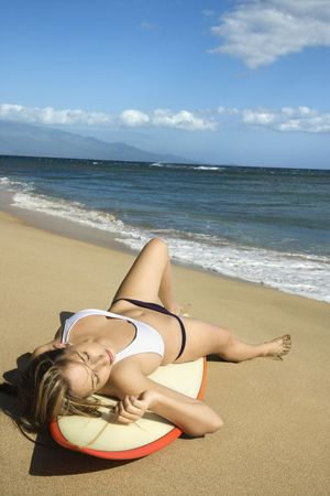 Sexy young Caucasian  woman in bikini lying on surfboard sunbathing at beach in Maui Hawaii. photo
