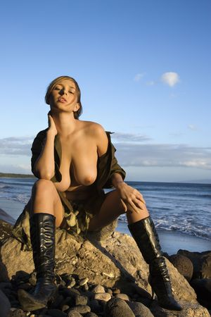 Portrait of sexy young Caucasian woman sitting on rocky coast with breasts exposed in Maui Hawaii. Stock Photo - 2188847