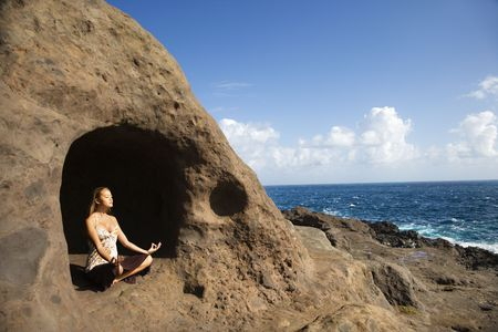 Young Asian woman mediatating in cave with coastline of Maui, Hawaii. photo