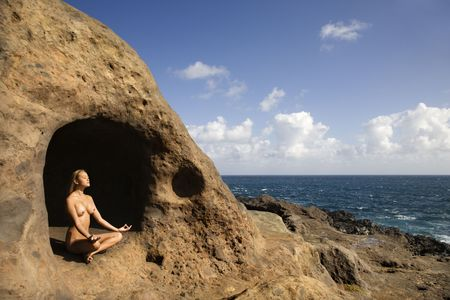 Young nude Asian woman mediatating in cave with coastline of Maui, Hawaii. Stock Photo - 2188855