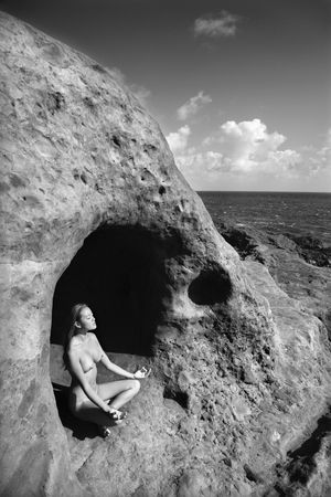 Young nude Asian woman mediatating in cave with coastline of Maui, Hawaii. Stock Photo - 2188916