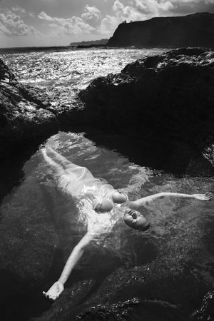 Young nude Asian woman floating in water with arms outstretched in Maui, Hawaii.