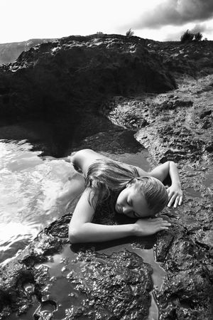 Young nude Asian woman partially submerged in water lying face down on rocky coast. Stock Photo - 2188906