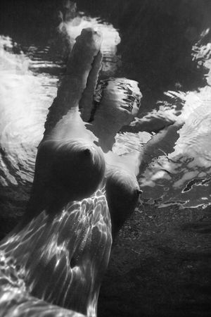 bare breasts: Underwater view of young Asian nude woman partially submerged sitting with hands behind head. Stock Photo