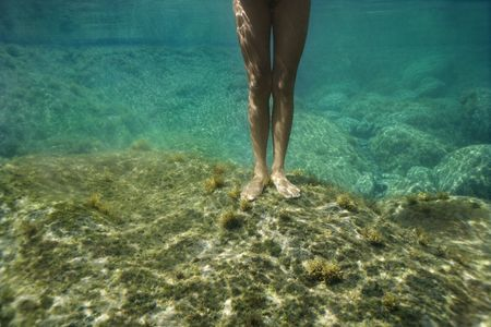 dipping: Feet and legs of young Asian  woman standing underwater.