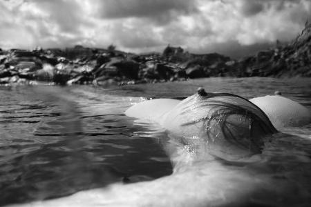 senos desnudos: Pechuga de j�venes de Asia mujer desnuda flotando en el agua en la costa rocosa en Hawai.
