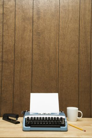 Vintage typewriter, coffee cup, pencil and stapler on desk. photo