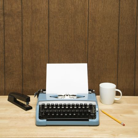 Vintage typewriter, coffee cup, pencil and stapler on desk. Stock Photo