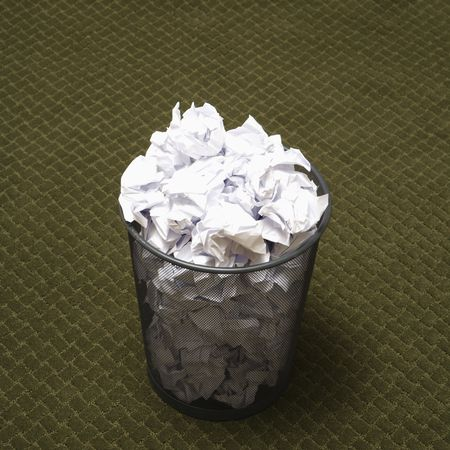 wadded: Wire mesh trash can filled with crumpled paper on green carpet. Stock Photo