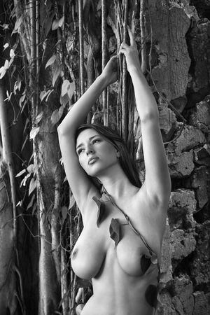 Close up of young adult  Caucasian woman holding onto vine in Maui.