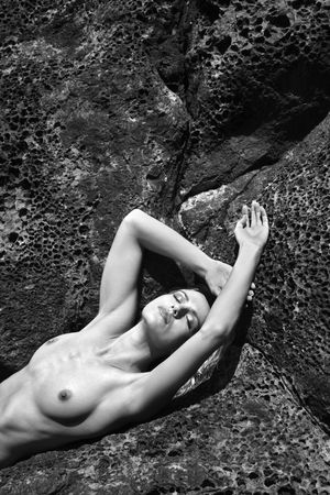 beach breast: Close up of young adult Caucasian  woman lying on rocks in Maui.