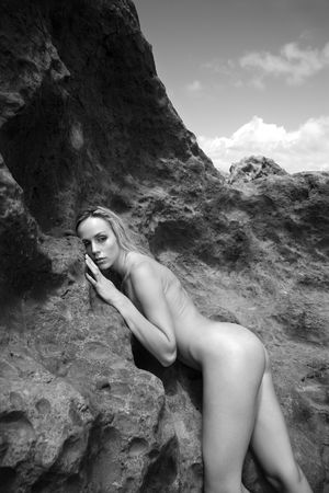 half nude: Young adult nude Caucasian woman standing and leaning on rocks in Maui.