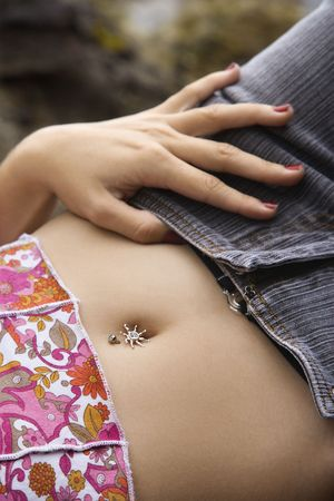 piercing: Close up of young Caucasian female lying down with hand on hip and bare midriff.