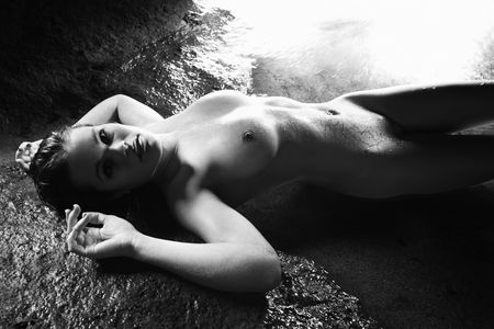 Young nude Caucasian woman lying down on wet rock looking at viewer.