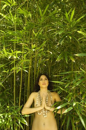 half nude: Nude young adult woman standing in bamboo with hands to chest in prayer position and looking up.