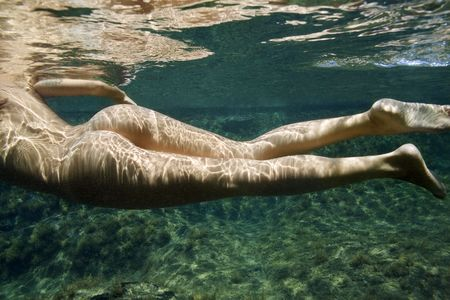 nude butt: Caucasian young nude female body swimming underwater. Stock Photo