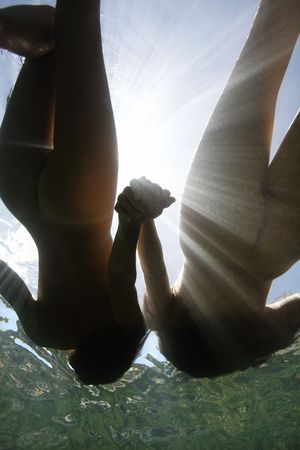 Two young nude women holding hands and floating underwater. photo