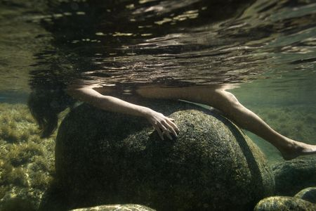 partially nude: Caucasian young nude woman partially submerged underwater lying on back on rock.