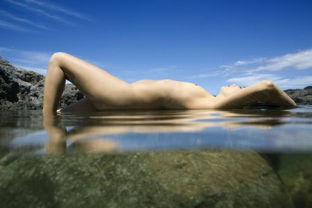 Caucasian young nude woman lying on back on rock in water. Stock Photo - 2188035
