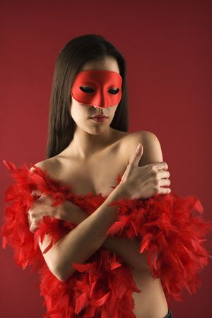 Partially  Caucasian woman wearing mask and boa. photo