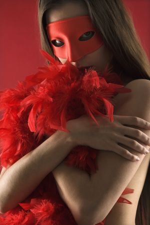 Partially  Caucasian woman wearing mask and boa photo