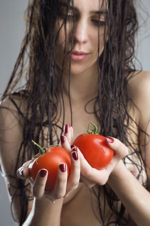 Topless Caucasian woman holding tomatoes. photo