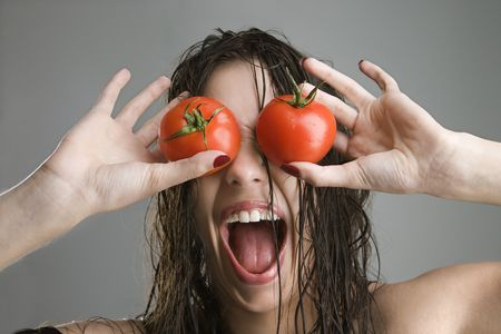 Caucasian woman with tomatoes covering her eyes. photo