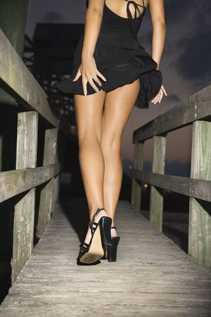 Back view of Caucasian mid-adult woman wearing little black dress and heels walking on wooden bridge. Stock Photo
