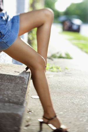Legs of Caucasian mid-adult woman wearing blue jean skirt and heels.