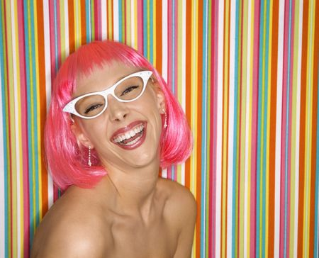 sassy: Portrait of attractive Caucasian young adult woman wearing pink wig against striped background making sassy expression looking at viewer. Stock Photo