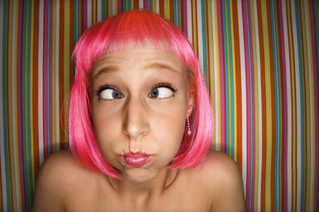 eyed: Portrait of attractive Caucasian young adult woman wearing pink wig against striped background making cross eyed expression.